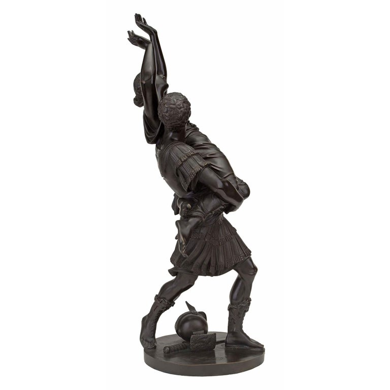 A striking French 19th century Louis XVI st. bronze statue of L'Enlevement des Sabines signed Raingo Frères. The high quality bronze is raised by a circular base where the soldier's helmet and sword are lying on the ground. The handsome soldier is