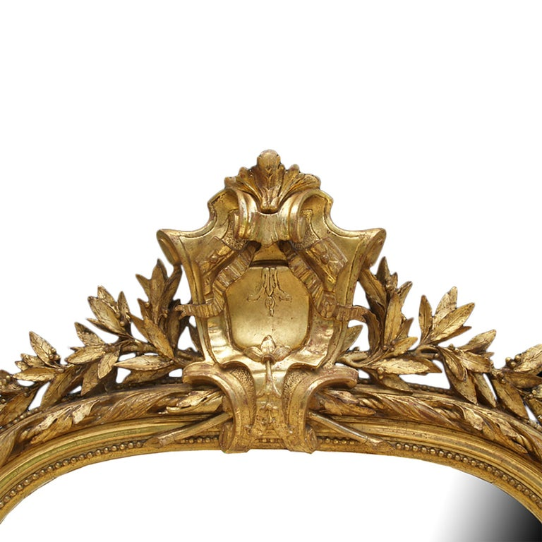 A spectacular and finely detailed French 19th century Louis XVI St. giltwood mirror with rich carvings throughout and all original gilt. The mirror has a most attractive twisted foliate garland carved border flanked by beaded rows. Each side has