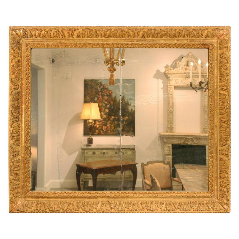 An attractive French 19th century Louis XVI St. giltwood mirror. The rectangular giltwood mirror with moulded frame has a dentil trim leading to its most prominent and richly carved acanthus leaf and foliate border. A solid band is followed by a