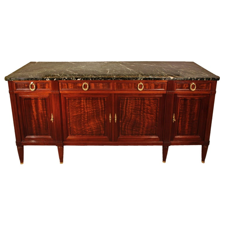 A fine quality French 19th century Louis XVI style mahogany and ebony buffet. The buffet is raised by circular fluted tapered legs ending with ormolu sabots. Above the straight frieze are four paneled doors with inlaid ebony trim and mottled border,