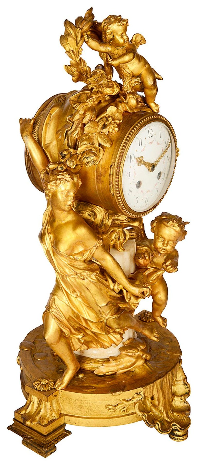 An enchanting late 19th century French gilded ormolu and marble mantel clock, depicting cherubs playing, one chasing a young girl, the other hiding amongst a wreath and foliage. The enamel clock face with an eight day duration, strikes on the hour