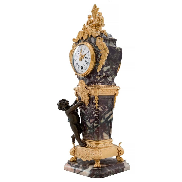 An exceptional French 19th century Louis XVI style ormolu, patinated bronze and Brèche Violette marble clock. The clock is raised by a square marble base with cut corners and a mottled border. The central ormolu support is raised by handsome paw