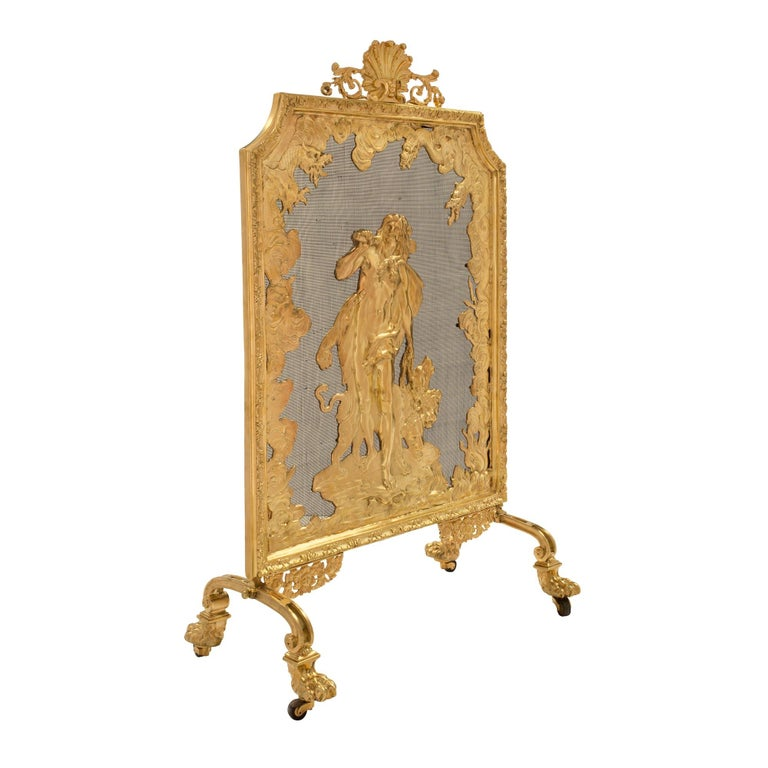 An elegant French 19th century Louis XVI style ormolu fireguard. The fireguard is raised by its original casters under handsome paw feet and scrolled legs. Above are beautiful pierced foliate scrolled movements centering the impressive and finely