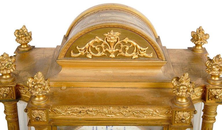 A good quality 19th century French gilded ormolu mantel clock, having an arched pediment with scrolling detail, six floral finials above column supports, beveled glass panels, a white enamel clock face with an eight day duration movement that chimes