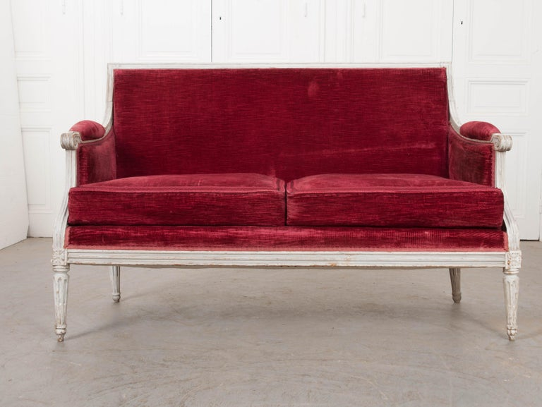 This lovely Louis XVI-style grey-painted settee, circa 1870s, is from France and upholstered in a rich red velvet with matching tape trim. This piece would look great in an entry or at the foot of a bed!