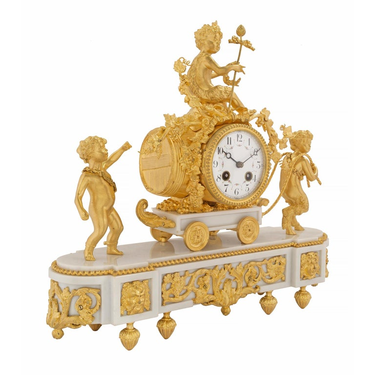 An elegant and high quality French 19th century Louis XVI style white Carrara marble and ormolu clock. The clock is raised by foliate topie shaped feet below the oblong shaped white Carrara marble base. The base displays a fine fitted pierced ormolu