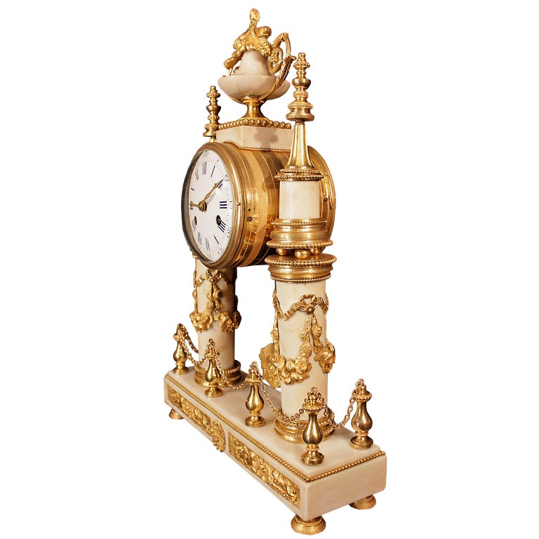 An exquisite French early 19th century Louis XVI style white Carrara marble and ormolu-mounted clock. Raised on ormolu supports the rectangular marble base with beaded trim and Clodion style plaques is centered by a floral mount. Above ormolu,