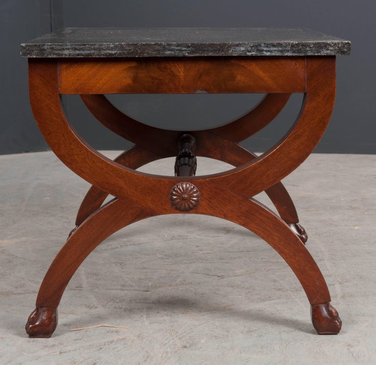 A refined coffee table, made in the French Restauration style at the end of the 19th century. The table is topped in a beautiful piece of black fossil marble. The curule-form base is braced by a turned mahogany stretcher that has been styled with