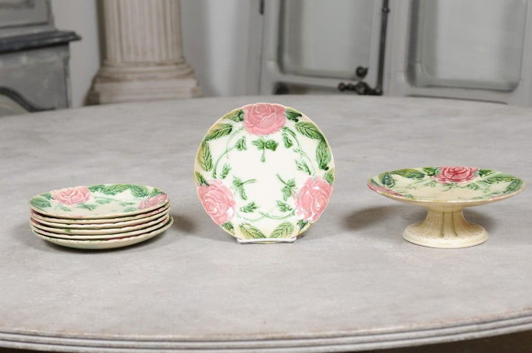 A French majolica compote and seven plates from the 19th century, with roses and foliage, priced and sold individually. Born in France during the 19th century, these majolica plates and compote charm our eyes with their slightly faded pink and green