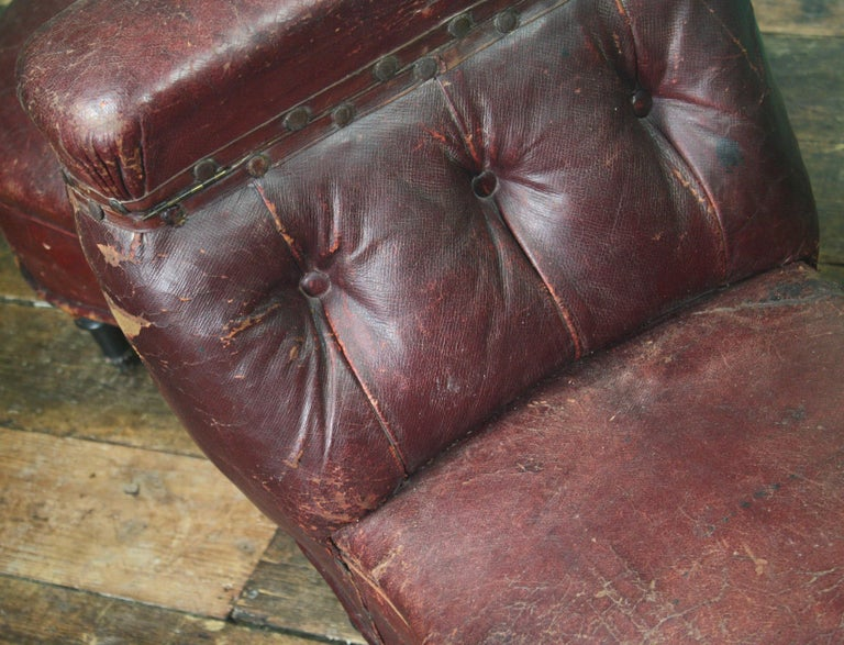 A rather curious double seated, maroon leather chair. The chair sits on six turned ebonised legs terminating on castors. The top of the backrest has a hinged compartment Late 19th century in age, likely to be French in origin. The chair has some
