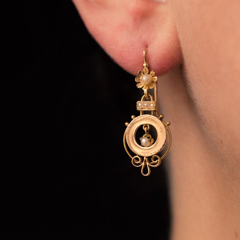 For pierced ears. Earrings in 18 karat rose gold, eagle's head hallmark. Pair of ear pendants, each one consists of a lever- back earring representing a daisy whose heart is a natural pearl. It retains a circular motif as a pendant with a chiseled