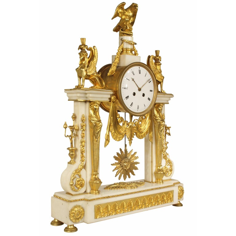 A stunning and important French 19th century neoclassical style ormolu and marble clock. The clock with white Carrara marble is heavily ornamented with finely chiseled ormolu mounts. The rectangular marble base is raised on ormolu feet and decorated