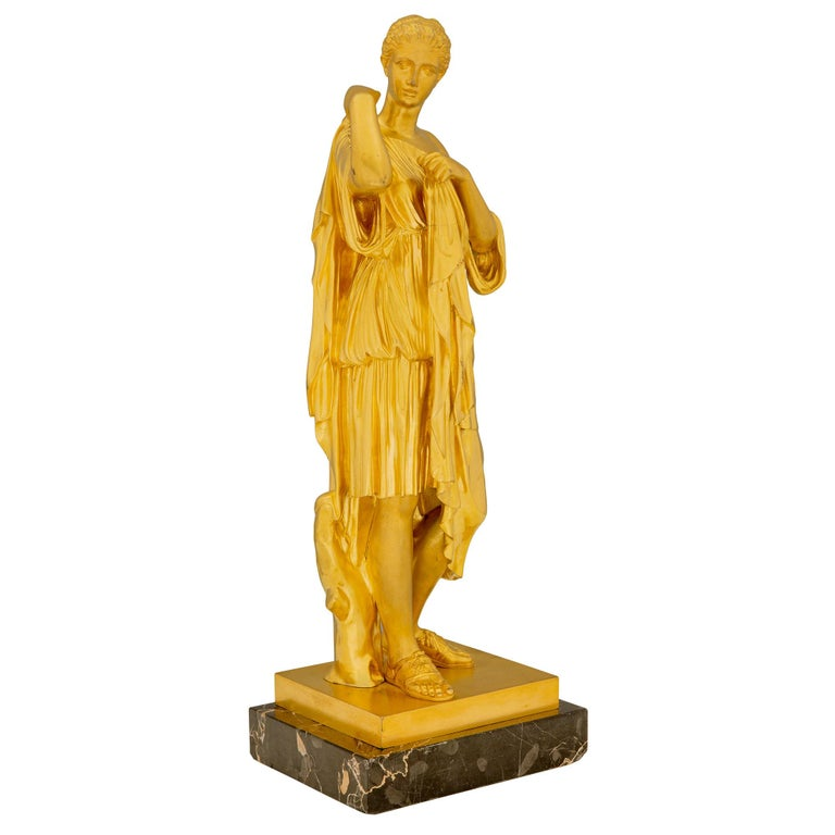 An extremely elegant French 19th century neoclassical st. ormolu and Portoro marble statue of a maiden. The statue is raised by a rectangular Portoro marble base where the beautiful maiden is standing next to a tree trunk. She is draped in a