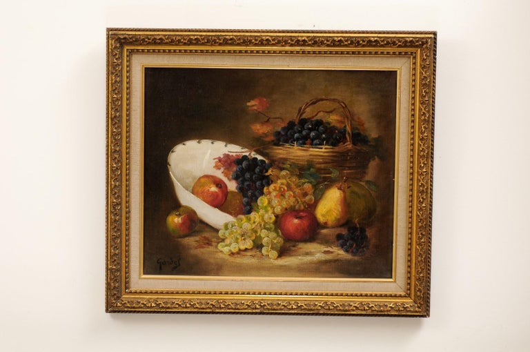 A French oil on canvas still-life painting from the 19th century, depicting fruits and set in giltwood frame. Created in France during the 19th century, this oil painting depicts a careful arrangement of mouth-watering grapes, pears and apples. The