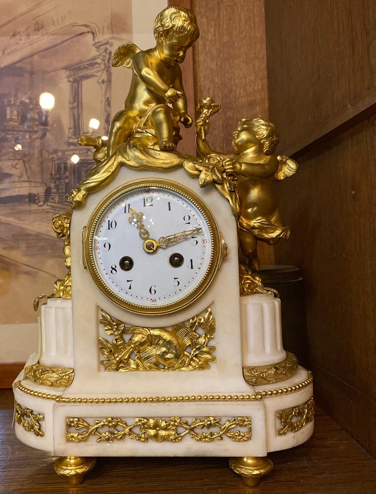 Delicious French white marble ormolu mantel clock resting on four turned feet supporting an oval marble base with raised garland decoration. Two gracious cherubs are seated upon the ormolu draped base. Striking every half hour and hour. Perfect