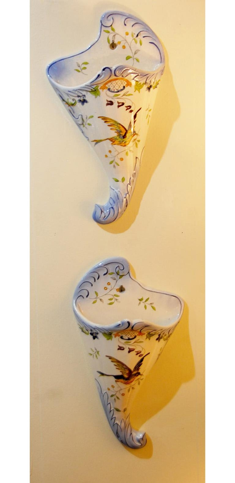 French 19th century Longchamp pair of faience hand painted wall pockets with bird and flower motifs, molded leaves to edges, cornucopia form. Crackleware glaze. Impressed mark: Longchamp Terre de Fer. Late 19th century.