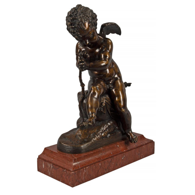A charming and very elegant French mid 19th century patinated bronze statue of a cherub, after Charles Gabriel Lemire. The statue is raised by a rectangular Rouge Griotte marble base with a concave top mottled border. Above is a sweet winged cherub,