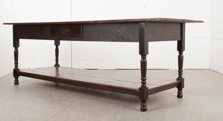 This wonderful Provincial walnut drapery table, circa 1890, is from Burgundy, France and features a plank top over an apron outfitted with a single drawer. The whole is supported on turned legs and bun feet. A roomy stretcher shelf allows for loads