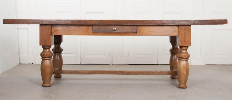 A robust, solid oak farmhouse table, done in a refectory style, from 19th century, France. Gnarled knots, beautiful grain, and an incredible range of textures give the thick tabletop its abundant character. The apron houses a small, single drawer,