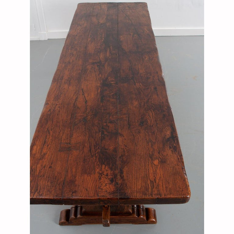 """Large slabs of solid oak were used to create this stunning, French oak trestle table. The primitive, 2-½"""" thick oak has achieved a remarkable patina over the course of its lifetime. Two shapely vertical supports are joined by a stretcher below the"""