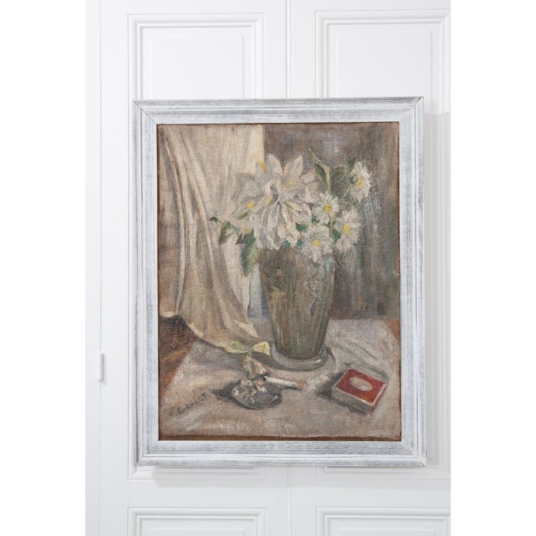 A softer palette, antique oil painting from 19th century, France. The work exhibits a vase holding dahlias and daisies, a cigarette and matches. The piece is set in a white and gray frame that works nicely with the painting. The artist has marked