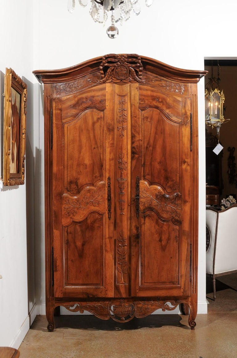 A French Transition style Provençal wedding armoire from the 19th century, with chapeau de gendarme top and carved motifs. Created in Provence during the 19th century, this Southern French wedding cabinet showcases the delicate transition of style