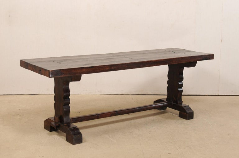 A French wooden console table from the 19th century. This elegant antique table from France has a rectangular-shaped top, just over 7 feet in length, which is supported by a pair of trestle legs (with curvy carvings down their sides), and braced