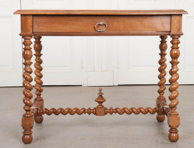 A fine French writing table, or desk, made of beautiful solid walnut, circa 1870. Four impeccably well-turned legs steal the show along with the table's twisted stretcher. The legs and stretcher have been created in a barley twist design and meet at