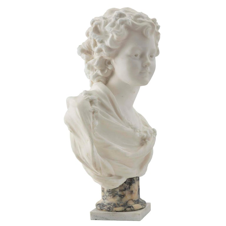 A high quality French 19th century white Carrara marble bust of a very lovely young lady. The bust is raised on a square white Carrara marble base below the fluted Bréche marble socle. The young lady is draped in classical attire accented with