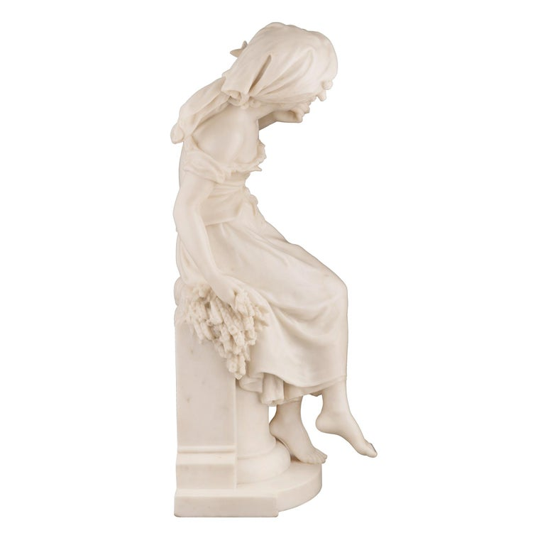 A stunning French 19th century white Carrara marble statue of a beautiful young maiden, signed Math Moreau. The statue is raised by a demi lune shaped tier with an elegant pedestal displaying a mottled border with a sickle and tied wheat sprigs at