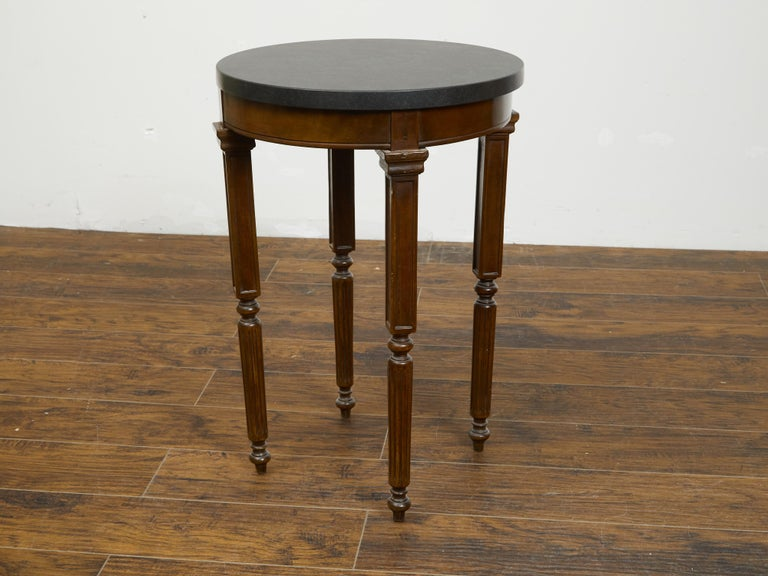 A French wooden guéridon table from the 19th century, with black marble top and unusual legs. Created in France during the 19th century, this guéridon table features a circular black marble top sitting above a simple apron. The table is raised on