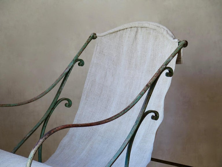 Wonderful, sturdy wrought iron rocking chair of generous proportions. The iron retains most of its original green paint, and is delicately adorned with curlicued details. Upholstered in heavy, natural-colored, antique linen. Possibly from Arras.