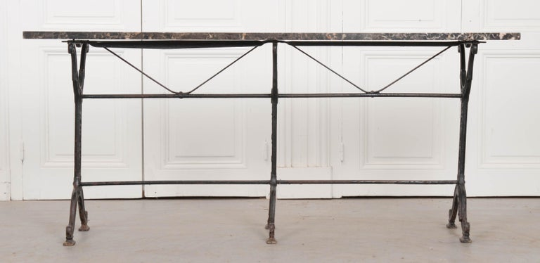 This classically styled French garden table is wonderful antique condition. The black stone top, with beautiful red and white striations, as well as some expected surface scratches, is an early 20th century addition to the late 19th century iron