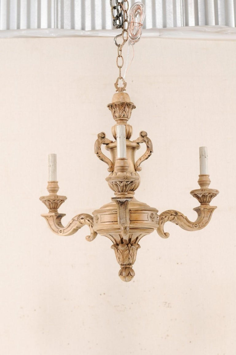 A French three-light shapely carved natural wood chandelier from the mid-20th century. This vintage chandelier from France features an ornately decorated central gallery with an urn-shaped carving, with pierced handles, atop the more bulbous mid