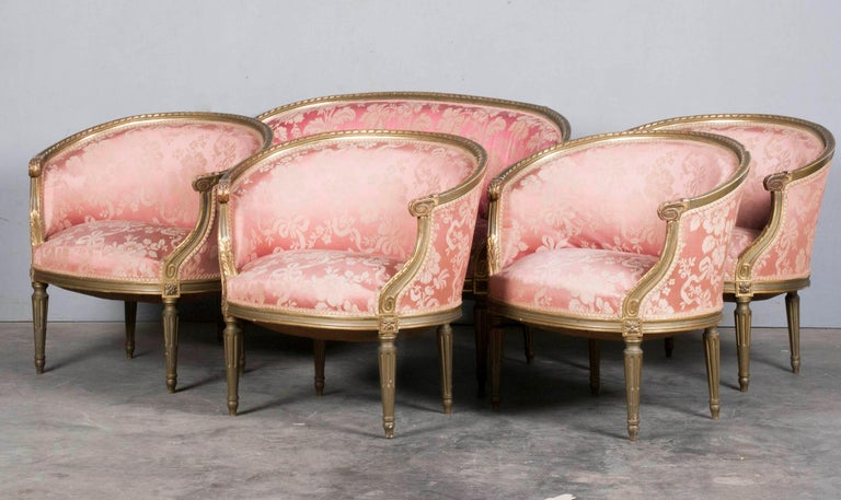 5-piece charming set of seating furniture. The set consists of 4 chairs and a sofa. The style is Louis XVI, this can be seen from the characteristics of the rotating ribbon in the carvings. The woodwork is partly gilt and partly green patinated.