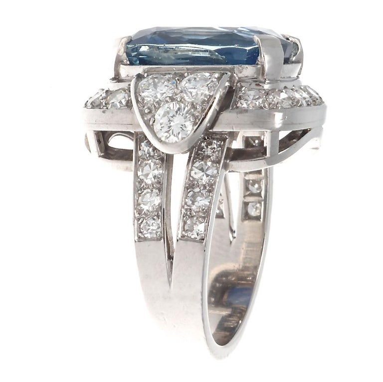 Parisian style represented by graceful symmetry and colorful design. Featuring a natural unheated 8.69 carat elongated cushion cut cornflower blue sapphire brilliantly set amidst geometric formations of diamonds. Crafted in platinum.  Ring size 5