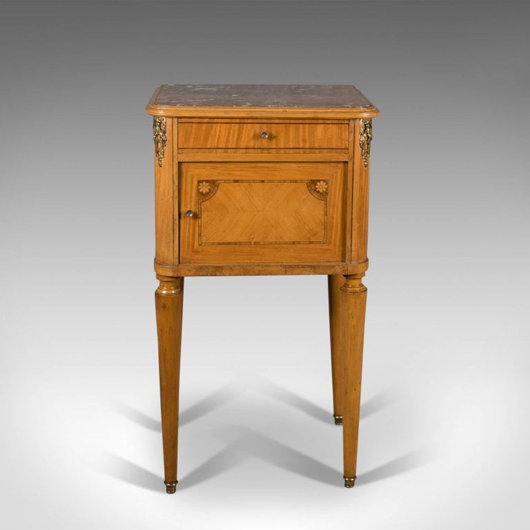 This is a French antique bedside cabinet, a marble top nightstand dating to the late 19th century, circa 1890.  Appealing biscuit tones to the light walnut finish Attractive grain in the quartered veneered decoration Well veined blush marble top