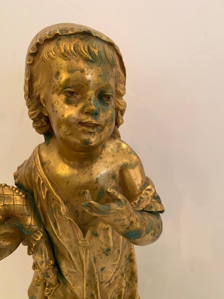 A gorgeous antique bronze figure of a young girl holding a clown doll and candle, signed Masse, (1855-1913) on the base and engraved