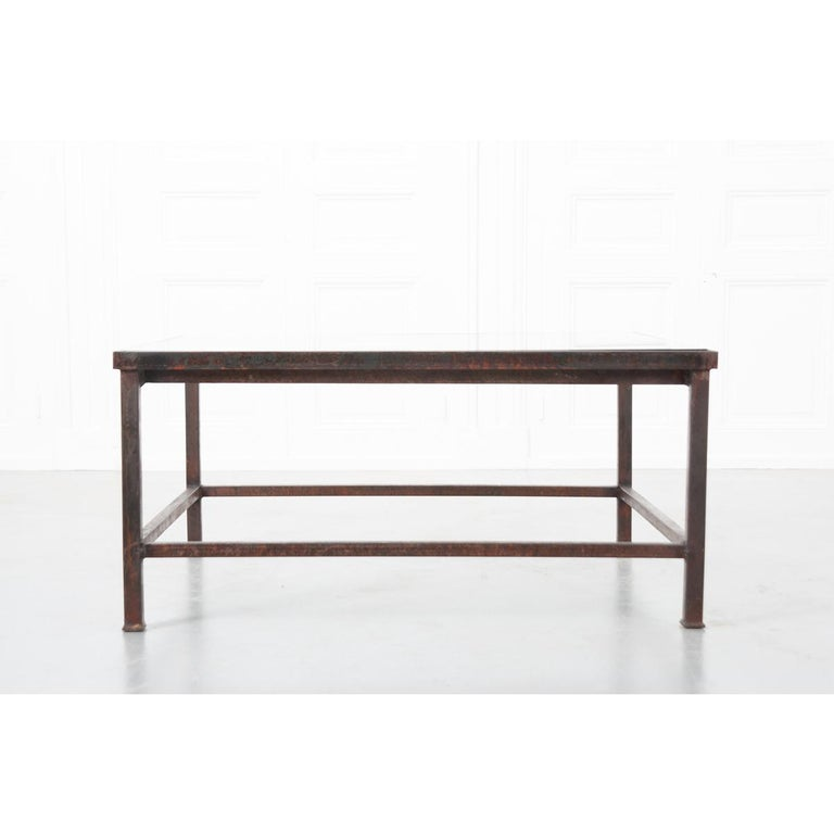 A wonderful marriage of old and new, this exceptional coffee or cocktail table has a newly fabricated base that incorporates a stunning architectural fragment, sourced from an antique French iron balcony surround, that is styled with scrolled