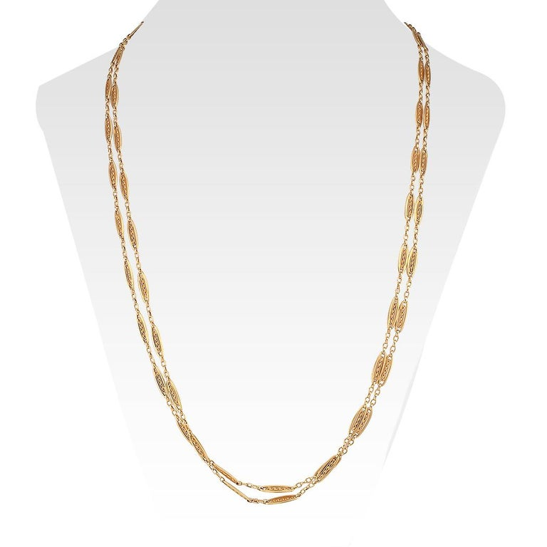 Antique French long gold chain necklace circa 1900. The 18-karat gold design comprises a series of handcrafted open work links completed by a slightly oversized clasp. We love the design of the links, their dimensionality, each encencapsulating a