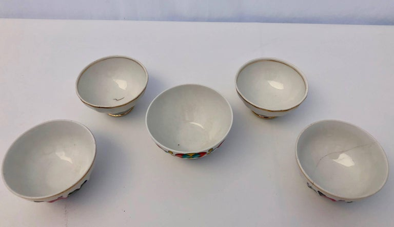 These small antique French bowls are not often found. There are five in the lot and all have a white background. A set of two have gold trim while another set of two are painted with a floral design and have gold trim at the top. A single bowl has a