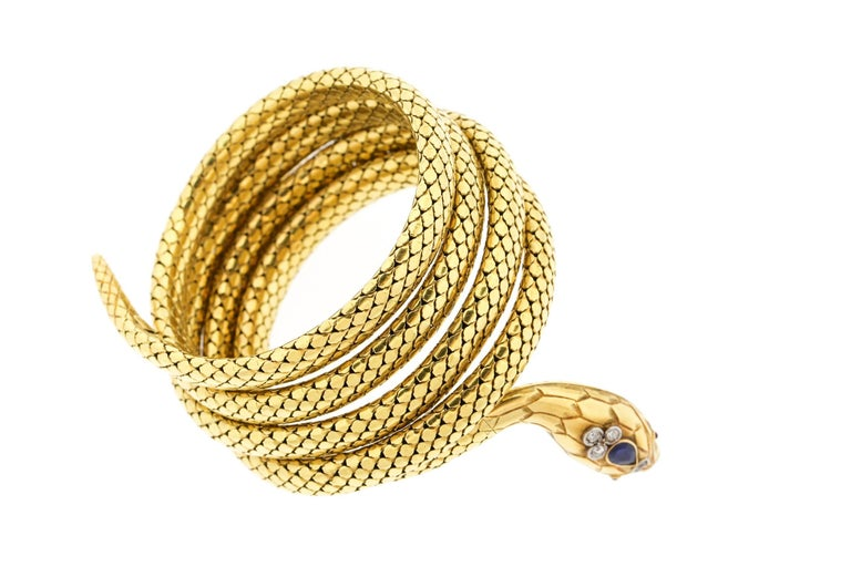 A late Victorian coiling 18k gold snake bracelet, made in France.  The bracelet wraps around the wrist 5 times, and is in a nice tight condition.  It has spring and the gold is silky smooth.  The snake's head is set with a blue sapphire weighing