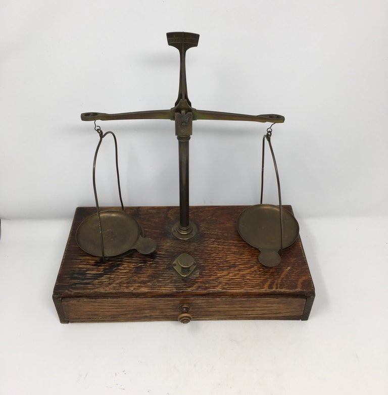Found in Southern France, these brass and wood apothecary scales where used in French pharmacies throughout the country. The scales and weights are brass housed on a wooden base with a drawer. Although some of the weights are missing, these scales