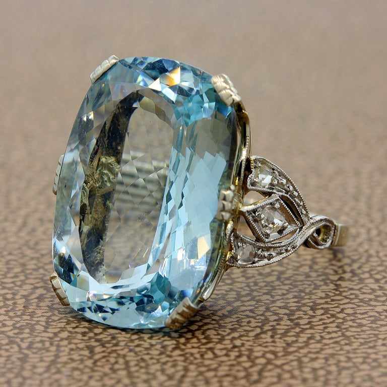 A French made ring featuring a lovely 12.55 carat aquamarine gem which is accented by round cut diamond. The ring is set in 18K white gold with French import marks.  Size 5 ¼