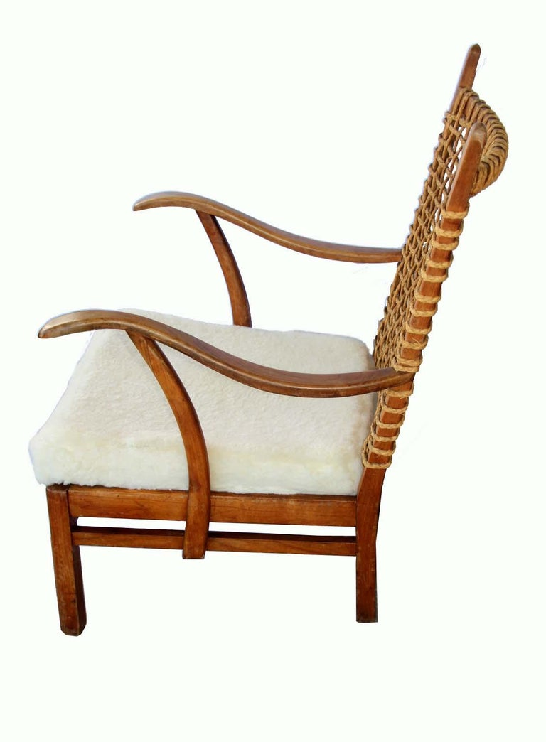 Unsigned Wood Armchair with a rope backing and soft lambskin seat(seat New cover). The lines are amazing and the patina and rope makes this chair Stand out as a really original and unique piece of furniture. Comfortable, stylish design brings warmth
