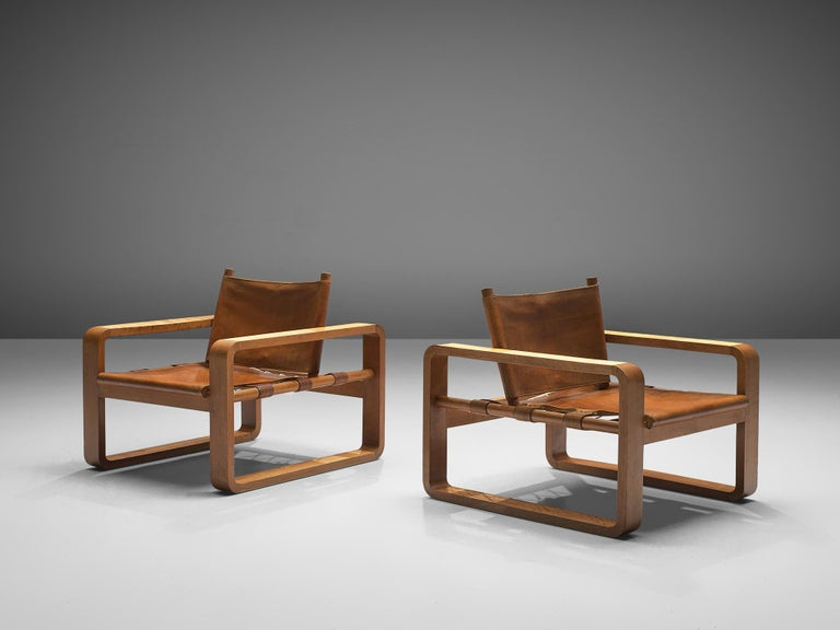 Pair of two lounge chairs, beech, leather and cotton rope, France, 1960s.  These comfortable armchairs in solid beech have unique square shaped armrests with rounded edges. The distinct horizontal shape of the frame creates a low and relaxed chair