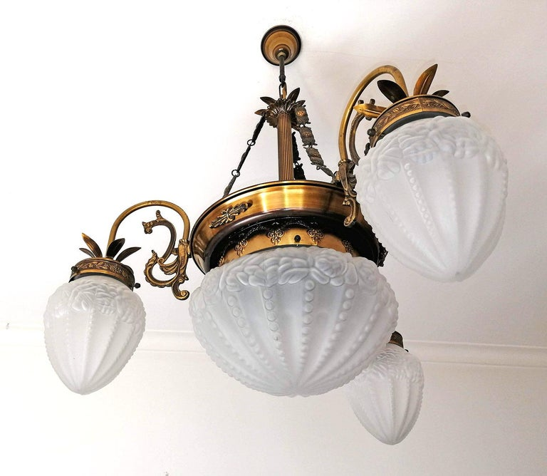 French Degué style Art Deco white frosted glass, 4-light brass chandelier/ gold and bronze color metal with patina. 4 bulbs E14 Good working condition / European rewired Measures: Diameter 28.5 in / 72 cm Height 32 in / 80 cm Glass shades: 6 in