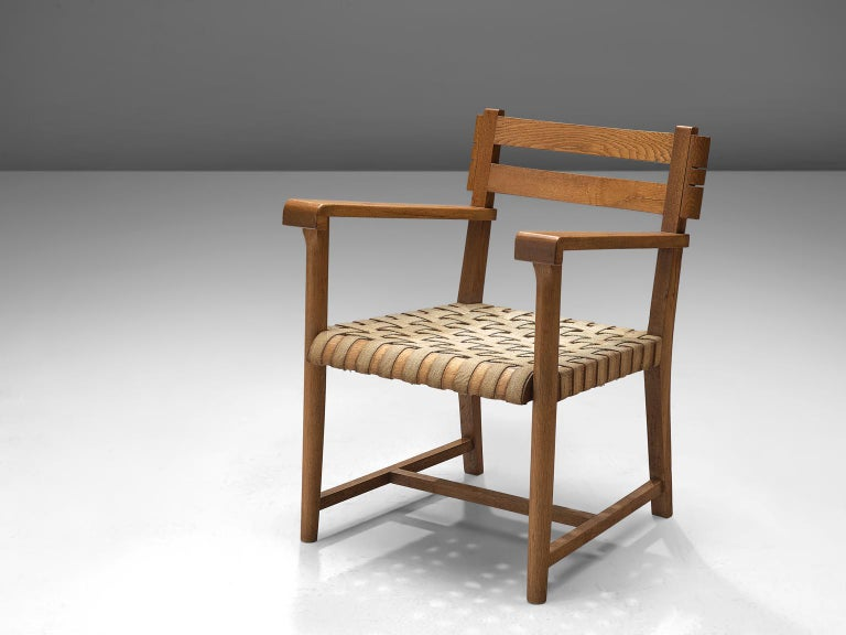 Armchair, oak and canvas straps, France, 1940s   This arm chair in the style of Charles Dudouyt (1885-1946) is both elegant and sturdy in their design. It might be the perfect seat to stand in a grand entrance or hall way. The roped seating on the