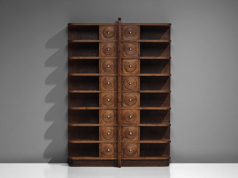 French Art Deco bookcase, patinated oak, brass, Europe, 1930s.  Large Art Deco bookcase in patinated oak in a symmetrical design. The bookcase has eight shelves left and right. The shelves have beautifully rounded edges, which give the bookcase a