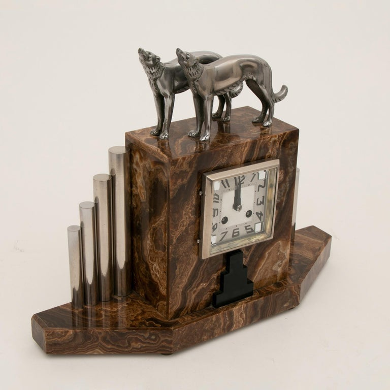 An impressive French Art Deco clock with silvered bronze Borzoi dogs and illuminating garnitures by Michel Decoux. Both dogs signed bronze.
